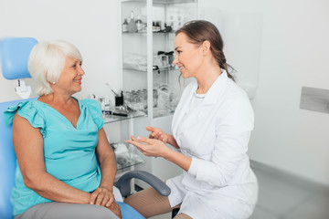 Doctor talking with aged woman in doctor's office. Medical support elderly patient