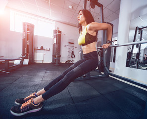 Beautiful athletic young woman making exercise at the gym. Young woman with muscular body.