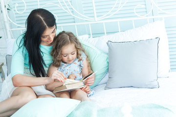 Young mother reading a fairy tale to her little sleepy daughter