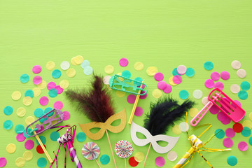 Purim celebration concept (jewish carnival holiday) over wooden green background.