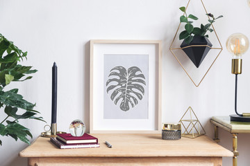 The room interior with mock up photo frame on the retro wooden shelf and hanging plant in design pot, tropical plant, candle and design coffe table with table lamp.