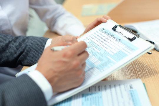 Man filling in U.S. Individual income tax return, tax 1040 at table.