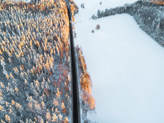 Aerial view of a car on winter road in the forest. Winter landscape countryside. Aerial photography of snowy forest with car on the road. Captured from above with a drone. Aerial photo. Car in motion