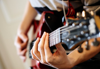 man playing rock on a red electric guitar on a Sunny day