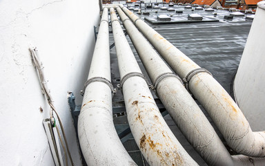 Pipes on the roof of a department store, which is also used as a parking lot for customers.