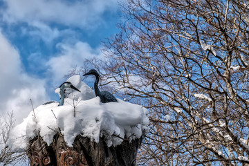 Wooden storks on a tree in the snow.