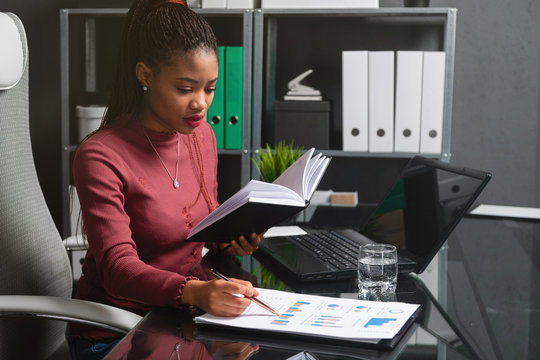 young African-American businesswoman working with documents and notebook at computer Desk in office