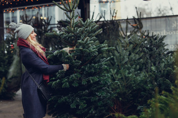 Pretty blonde girl looking for perfect Christmas tree to buy on the tree shop, outdoor. Girl using hand for check the quality, copy space - Image