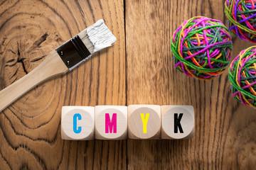 """Buchstaben """"CMYK"""" auf Würfeln in den entsprechenden Farben"""