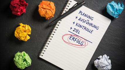 Motivierende Begriffe auf einem Notizbuch am Arbeitsplatz