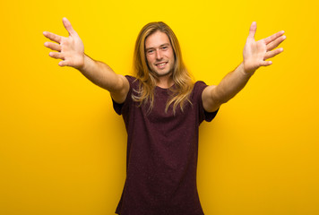 Blond man with long hair over yellow wall presenting and inviting to come with hand