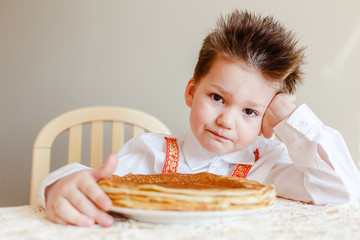 Russian Maslenitsa. boy is sitting at a table with a plate of fried pancakes . pancakes on Shrove Tuesday