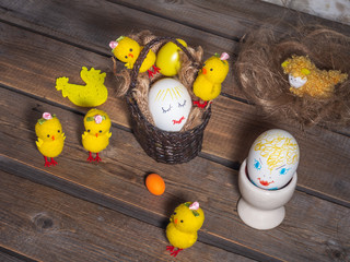 Easter fun picture with painted faces on the eggs, toy chickens are located on a wooden old background.