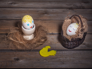 Fun picture with eggs with painted faces. One is in a wicker basket, and the other is on an egg holder.