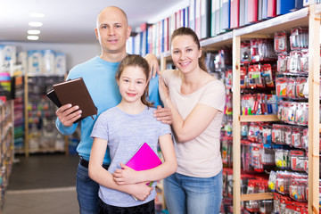 parents and daughter choose notebook