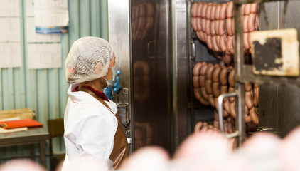 Female controlling hot processing of sausages