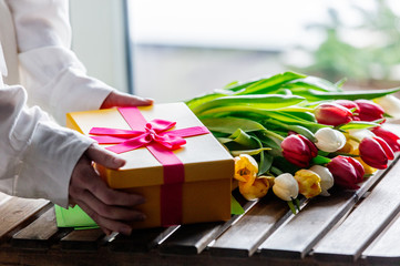 wrapping beautiful tulips near gift box on wooden table