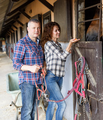 Mature smiling couple with girth feeding a horse at stable