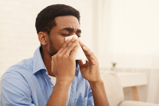African-american man man has runny nose at home