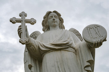 the angel in the hands of a cross, the background is overcast