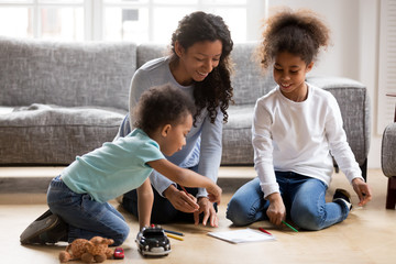 Happy black single mom and 2 mixed race kids draw with colored pencils on warm floor together, african mother baby sitter helps children son daughter playing having fun at home, creative family hobby