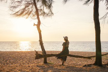 Happy young woman enjoying freedom  sitting on log viewing sunset on the sea sky sunset background