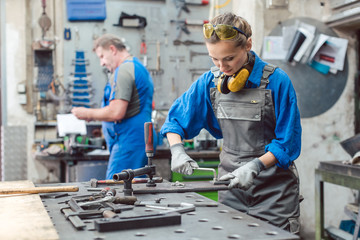 Man and woman working together in metal workshop with their tools
