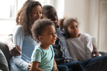 Happy black family with children sitting on couch watching tv together, african american parents embrace kids relaxing on sofa laughing enjoying funny cartoons or movie having fun on weekend at home