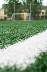 White line on artificial green field against football gate on background, low angle view