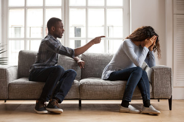 Angry black husband arguing yelling blaming upset wife of problems, jealous distrustful dominant african american boyfriend controlling shouting at sad girlfriend, quarrelling family fight at home