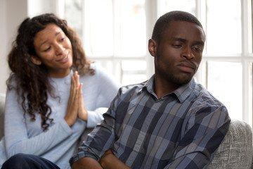 Guilty african american woman apologizing black husband sulking refusing to make peace after fight, mixed race wife asking for forgiveness begging husband to forgive saying sorry, apology concept