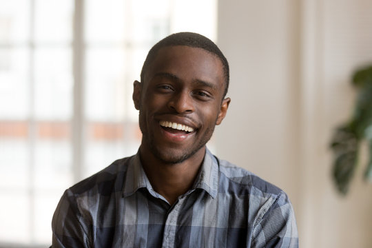 Cheerful african american millennial man with happy face looking at camera at home, head shot of smiling young black single guy laughing posing indoors, confident charming male person portrait