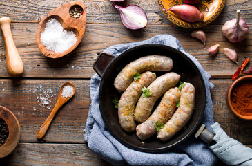 Raw white sausage on a wooden background with spices.