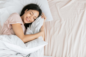 nice girl is laughing while sleeping, top view phoro. copy space.