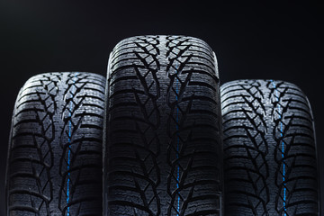 Set of new winter tires on black background with contrasty lighting. Close up product photograph of unused tyres