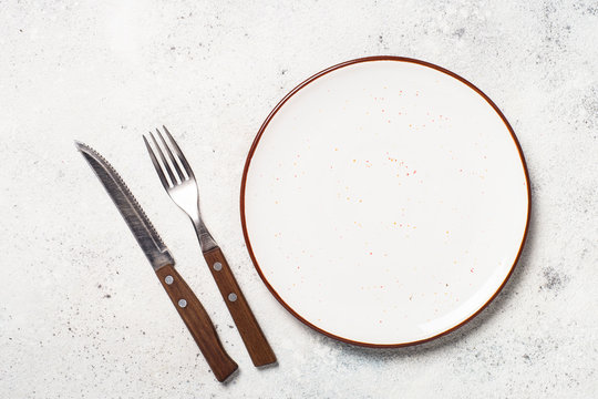 White craft plate, cutlery and napkin on white stone table.