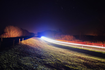 Long exposure of cars with light trails at night in the landscape nature. German Baltic Sea Darßer Ort, Weststrand coastline at Fischland-Darss-Zingst