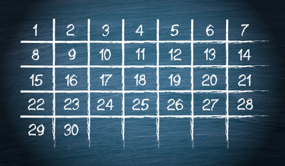 Monthly calendar with 30 days on blue chalkboard background