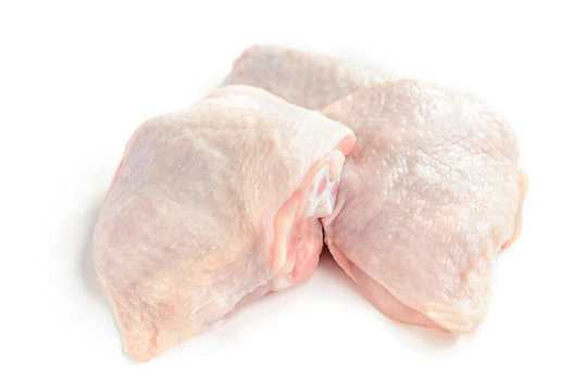 Raw chicken thighs isolated on white background.