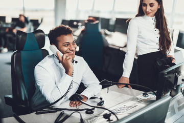 Smiling dispatcher talking by phone on work place