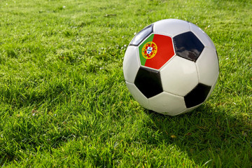 Football on a grass pitch with Portugal Flag