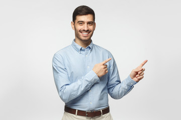 Happy smiling young business man pointing away, isolated on gray background