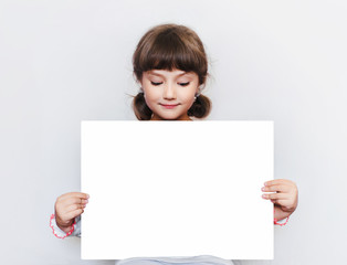The little girl is holding a blank sheet of paper. Education. Advertising. Copy space. Place for text.