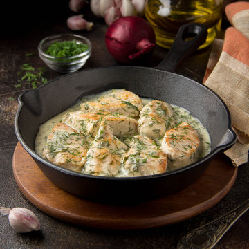 Chicken fillet or Turkey breast in creamy sauce with dill and garlic, in cast iron black pan on dark background. Delicious homemade food