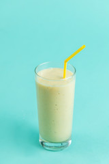Spoed Foto op Canvas Milkshake white smoothie from bananas. a portion of yogurt. close up photo. isolated blue background. drink for happy mood