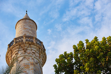 Top of the minaret of the mosque against the blue sky with a green tree