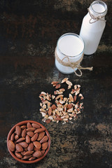 Almond milk in a glass and bottle. Fresh raw almonds.