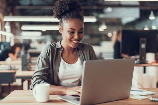 Beautiful afro american lady working on laptop in modern office