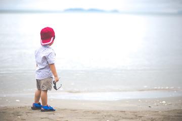 Asian boy walking the tropical beach, Happy little boy walking near the sea