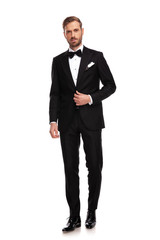 handsome businessman standing and buttoning black suit